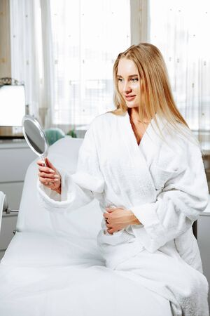 Beautiful young woman is looking into the mirror and smiling while sitting at the cosmetician