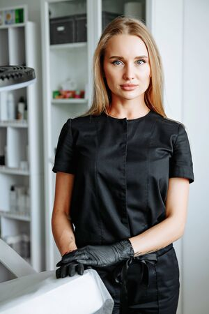 Caucasian cosmetologist standing in black coat near placard with drawn eye at cosmetology cabinet. Concept of qualitative medical worker, beauty salon and permanent makeup.