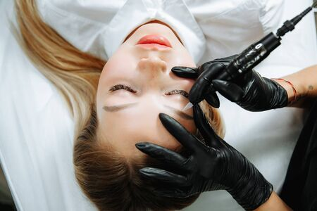 Close up of woman lying on couch at beauty salon with closed eyes and enjoying when cosmetologist making eyeliner permanent make up. Professional wearing black gloves and holding speciality tool. Stockfoto