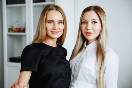 Two successful confident beauty salon female owners looking at camera. Cheerful female beautician is working with cosmetology.
