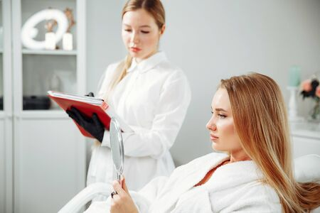 Consultation in cosmetology clinic. Female beauty doctor talking with patient. A young girl tells what she wants change in her face. Client shows on himself. Doctor listening carefully Фото со стока