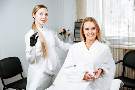Young female client received cosmetic face treatments in clinic of aesthetic medicine, looking in mirror at results Фото со стока