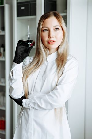 Doctor in pink gown and gloves holds syringe in medical office, ready for making injections. Cosmetologist before anti ageing procedure for her client. Aethetic medicine, skin care and cosmetology.