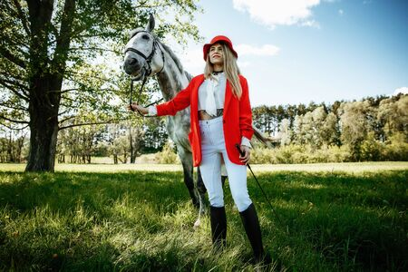 beauty blondie woman in red jacket and red hat with horse in the field, effect of toning. Equestrian sport concept. Fashion photoshoot