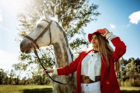 Beautiful young girl with blond hair in a red jacket with a fringe , wearing red hat, smiling and stroking her horse in summer field. equestrian sport concept