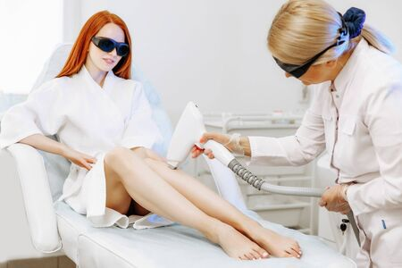 Body Care. Legs Laser Hair Removal. Beautician Removing Hair Of Young Woman's Leg. Laser Epilation Treatment In Cosmetic Beauty Clinic. Health And Beauty Concept.