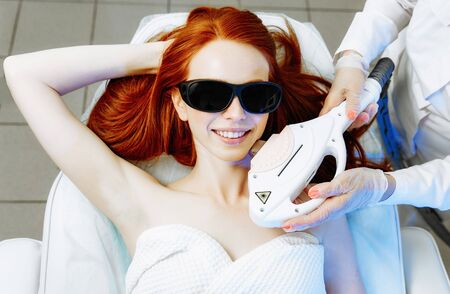 Woman undergoing hair removal procedure with laser epilator in salon. Laser epilation concept Фото со стока - 128258400