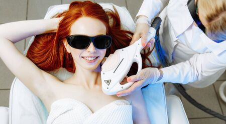 Pretty young woman receiving laser hair removal epilation on face. laser skin care concept Фото со стока - 128258402
