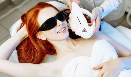 Pretty young woman receiving laser hair removal epilation on face. laser skin care concept