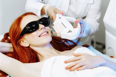 Pretty young woman receiving laser hair removal epilation on face. laser skin care concept Фото со стока - 128258448