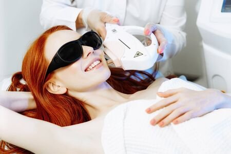 Woman undergoing hair removal procedure with laser epilator in salon. Laser epilation concept Фото со стока - 128258446