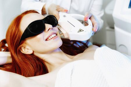 Laser hair removal from the face. Woman in the clinic of aesthetic medicine. Beautiful red hair woman having her facial hair removed by female beautician. Stock Photo