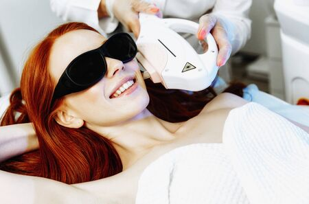 Pretty young woman receiving laser hair removal epilation on face. laser skin care concept Фото со стока - 128258450