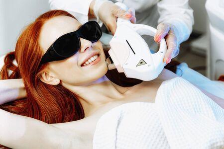 Depilazione laser dal viso. Donna nella clinica di medicina estetica. Bella donna dai capelli rossi che si fa rimuovere i peli del viso dall'estetista femminile.