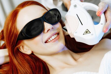 Laser hair removal from the face. Woman in the clinic of aesthetic medicine. Beautiful red hair woman having her facial hair removed by female beautician.