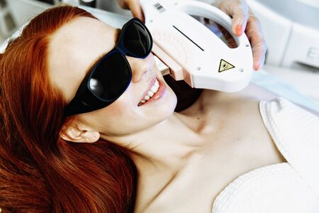 Pretty young woman receiving laser hair removal epilation on face. laser skin care concept Фото со стока - 128258462
