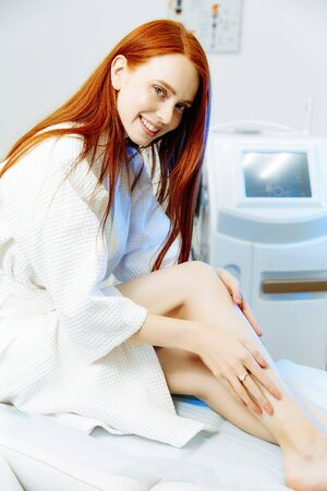 Medical beauty laser cosmeology procedure. Red hair caucasian beautiful woman sitting in white bathing robe at salon. Woman skincare technology. Hair removal.