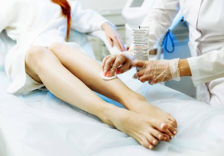 Preparation for laser epilation. Close up of aesthetician in sterile gloves putting gel on woman shin with brush Фото со стока - 128258532