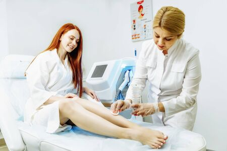 Doctor removed the remains of gel after a legs laser epilation from young woman Фото со стока - 128258531