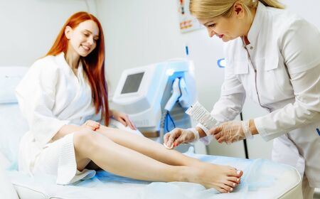 Doctor removed the remains of gel after a legs laser epilation from young woman Фото со стока - 128258536