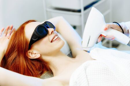 Body Care. Underarm Laser Hair Removal. Beautician Removing Hair Of Young Womans Armpit. Laser Epilation Treatment In Cosmetic Beauty Clinic. Hairless Smooth And Soft Skin. Health And Beauty Concept. Red hair woman lies on a couch with glasses and smiles