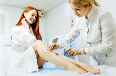 Preparation for laser epilation. Close up of aesthetician in sterile gloves putting gel on woman shin with brush Фото со стока - 128258595