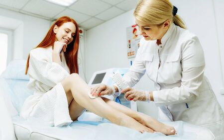 Preparation for laser epilation. Close up of aesthetician in sterile gloves putting gel on woman shin with brush Фото со стока - 128258603