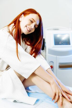 Young red hair woman with slim body and smooth clean skin sitting on the chair in the beauty clinic and smiling. Laser hair removal concept Фото со стока