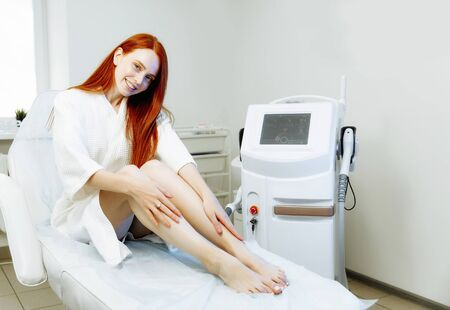Laser epilation, sugaring and cosmetology. Hair removal cosmetology procedure. Laser epilation and cosmetology. Cosmetology and SPA concept. Pretty red hair woman in the clinic Фото со стока - 128258700