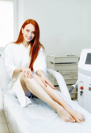 Laser epilation, sugaring and cosmetology. Hair removal cosmetology procedure. Laser epilation and cosmetology. Cosmetology and SPA concept. Pretty red hair woman in the clinic Фото со стока - 128258710