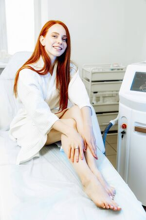 Laser epilation, sugaring and cosmetology. Hair removal cosmetology procedure. Laser epilation and cosmetology. Cosmetology and SPA concept. Pretty red hair woman in the clinic