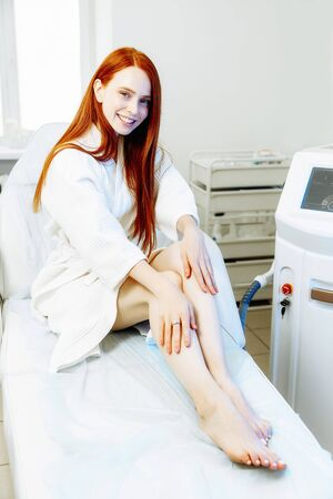 Medical beauty laser cosmeology procedure. Red hair caucasian beautiful woman sitting in white bathing robe at salon. Woman skincare technology. Hair removal. Фото со стока - 128258716