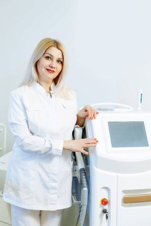A woman tunes a laser hair removal machine. She poses for a photo. It is located in a modern beauty salon. Фото со стока - 128258747