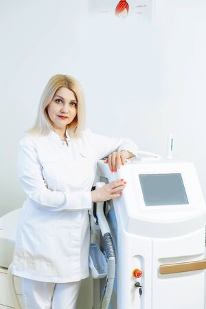 A woman tunes a laser hair removal machine. She poses for a photo. It is located in a modern beauty salon. Фото со стока - 128258746