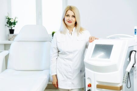 A woman tunes a laser hair removal machine. She poses for a photo. It is located in a modern beauty salon.