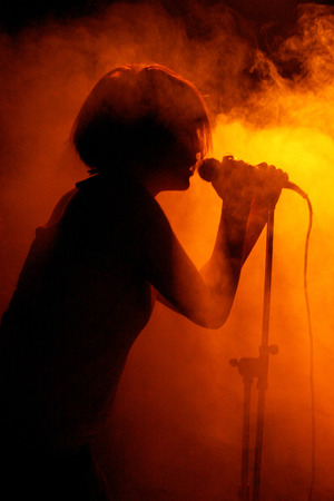 Concert photo of female singer silhouette holding microphone Redactioneel