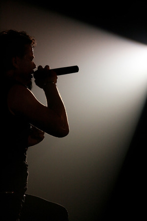 singer silhouette: Concert photo of male singer silhouette holding microphone
