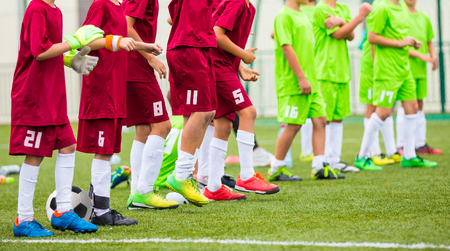 kids outside: Football match for children. Training and football soccer tournament. Children stand in a row Stock Photo