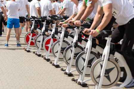 stationary: Stationary spinning bicycles outdoor in sunny day. aerobic meeting