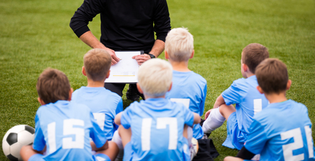youth sports: soccer football coach tactic strategy speech. kids listening coach strategy speech. Stock Photo