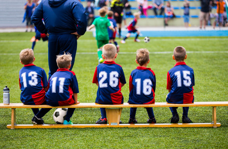 balones deportivos: Partido de fútbol de fútbol para los niños. Niños esperando en un banco. Foto de archivo