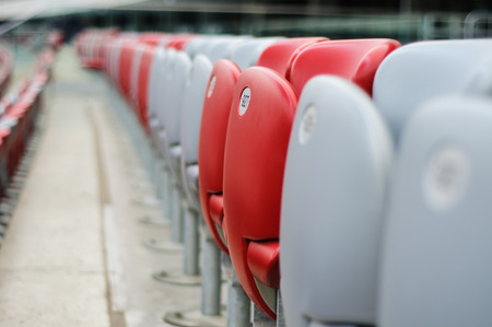 red chair: Several rows of red and white stadium seats