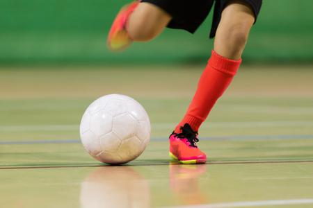 niño juega fútbol sala fútbol de fútbol en el salón de los deportes Foto de archivo