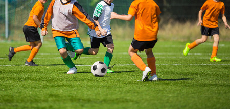 training shoes: Football soccer match for children. kids playing soccer game tournament. physical education classes at school. Stock Photo