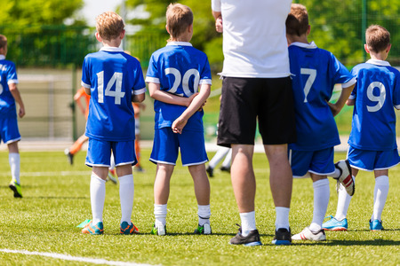 Die Jungen und Fußball-Trainer beobachten Fußballspiel. Jugendersatzspieler bereit zu spielen Lizenzfreie Bilder