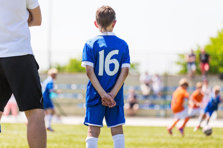 kids football: Young boy and soccer coach watching football match. Youth reserve player ready to play