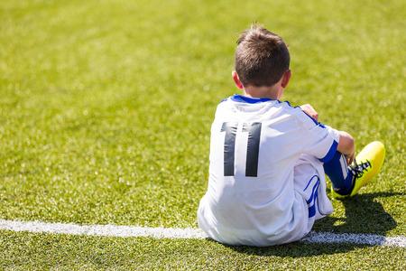 Jongen kijkt voetbalwedstrijd. Jeugd reserve speler van het voetbal academy klaar om te spelen