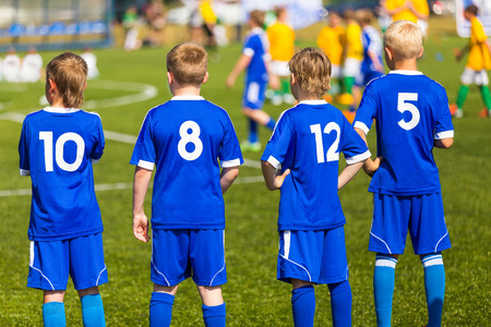young boys: Football soccer match for children. Kids waiting on a bench. Stock Photo