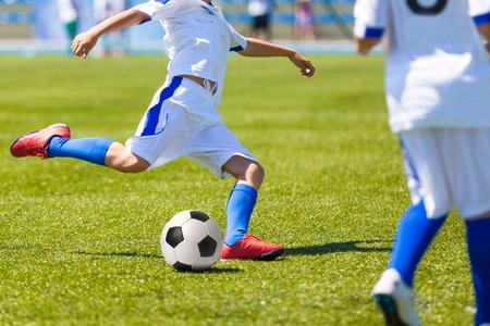 graczy grających piłka nożna gry. Przebiegu gracze w niebieskich i żółtych mundurach Zdjęcie Seryjne