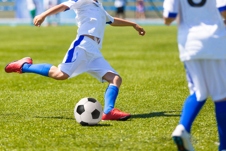 soccer sport: players playing football soccer game. Running players in blue and yellow uniforms Stock Photo